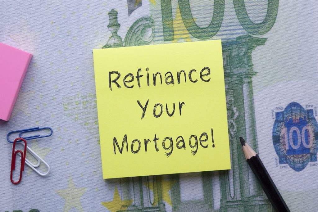 Refinance Your Mortgage written on note with pencil and office supplies. Business Concept.