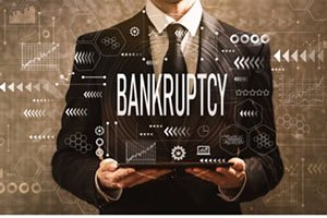 man in suit holding a sign that says bankruptcy